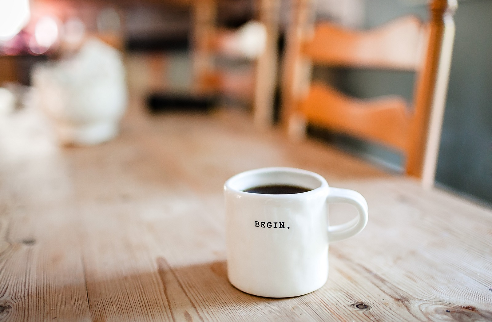 "Photo of a coffee mug on a wooden table the words ""Begin."" on the front"