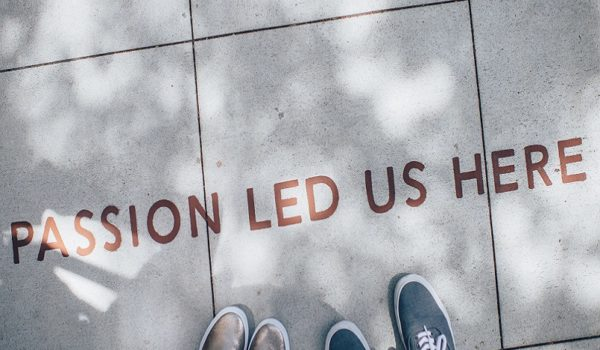 Photo from Websites with Danielle blog post showing two people's feet standing on tile that says passion led us here
