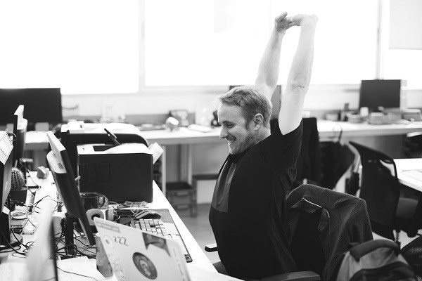 Photo of a man sitting at a desk stretching his arms, shoulders, and back on the blog post How to move more throughout your day, especially if you sit at a desk, written by Websites with Danielle